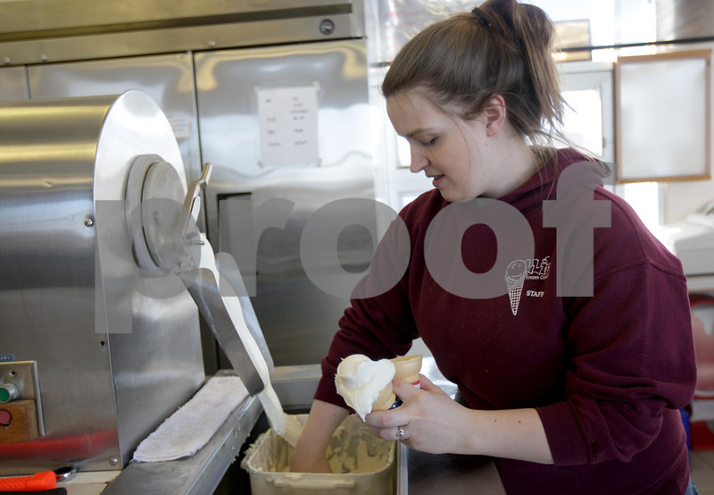 Monica Maschak - mmaschak@shawmedia.com<br /> Employee Tiffani Cordle scopes vanilla custard onto two cones at Ollie's Frozen Custard's opening day on Wednesday, February 26, 2014. They are currently only serving chocolate, vanilla and strawberry flavors.