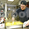Monica Maschak - mmaschak@shawmedia.com<br /> Catering Chef Seth Deathrage stirs the au gratin potatoes before putting them back in the oven at the Voluntary Action Center on Wednesday, February 19, 2014. Deathrage and three other chefs make dinners for the inmates at the DeKalb County Jail everyday.