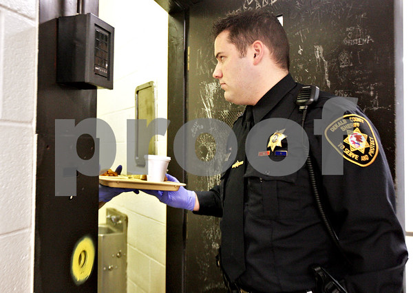 Monica Maschak - mmaschak@shawmedia.com<br /> Deputy Tim Smith hands out a lunch tray to an inmate at the DeKalb County Jail on Tuesday, February 25, 2014.