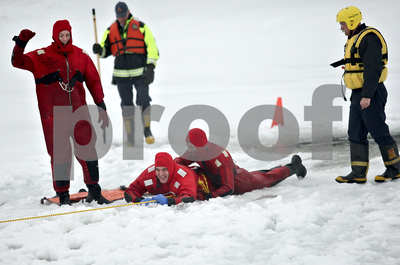 Monica Maschak - mmaschak@shawmedia.com<br /> Firefighter Mike Hardesty (left) relays a signal to the crew pulling firefighters Adam Honiotes and Evan Rhule out of the water during an ice rescue training at Sycamore Park on Thursday, February 20, 2014.