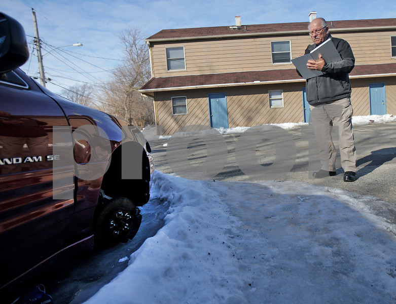 Monica Maschak - mmaschak@shawmedia.com<br /> Crime Free Housing Inspector Mike Stuckert notes a car without a wheel, which is a code violation, on a DeKalb rental property on Tuesday, February 25, 2014.