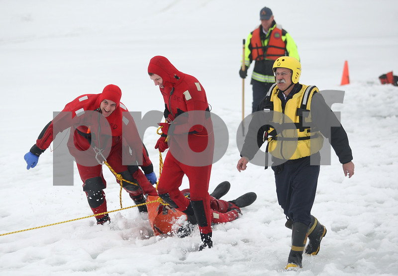 Monica Maschak - mmaschak@shawmedia.com<br /> Firefighter Adam Honiotes (left) and intern firefighter Evan Rhule pull firefighter Mike Hardesty from the water with the supervision of Fire Chief Pete Polarek (right) during an ice rescue training at Sycamore Park on Thursday, February 20, 2014.