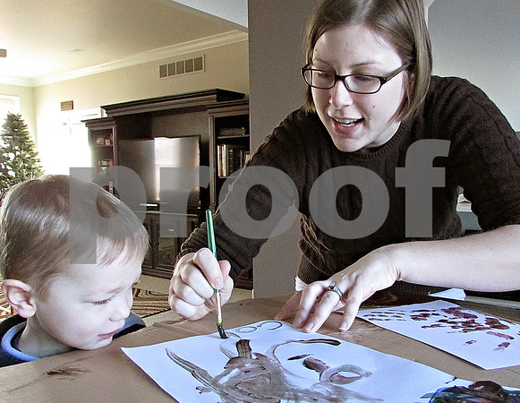 Andrea Azzo – aazzo@shawmedia.com<br /> <br /> Sycamore resident Sara Jennings shows her 3-year-old son, Cohen, how to paint Monday at home. Schools were closed because of the cold weather.
