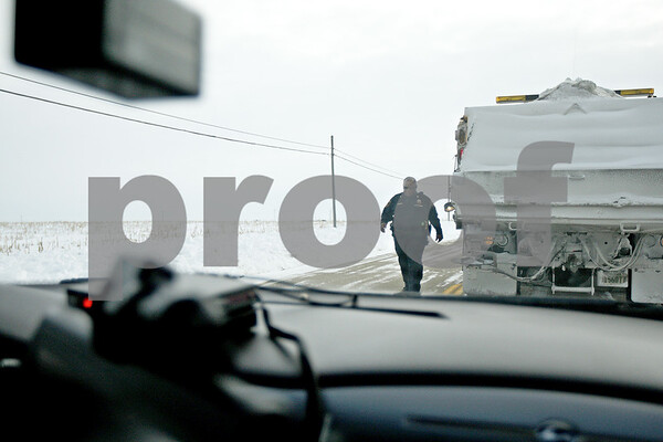 Monica Maschak - mmaschak@shawmedia.com<br /> DeKalb County Sheriff Sergeant Van Bomar returns to his squad car after talking with a plow truck driver blocking a road in Malta on Tuesday, January 7, 2014.
