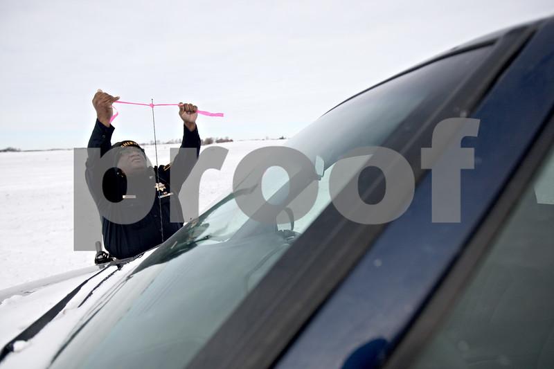 Monica Maschak - mmaschak@shawmedia.com<br /> DeKalb County Sheriff Sergeant Van Bomar tags an abandoned truck with a pink ribbon on Rt. 38 in Malta on Tuesday, January 7, 2014.