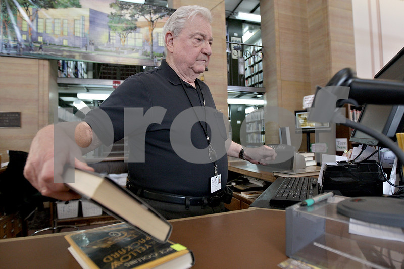 Monica Maschak - mmaschak@shawmedia.com<br /> Assistant Circulation Clerk Jim Webster checks books back into the system at DeKalb Library on Thursday, January 2, 2014.