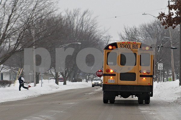 Rob Winner – rwinner@shawmedia.com<br /> <br /> A student is seen crossing the street after a bus stop on Somonauk Street in Sycamore, Ill., Thursday, Jan. 9, 2014. A new law that took effect this month allows school districts to install video cameras on buses to catch vehicles that pass stopped buses while dropping off or picking up students.