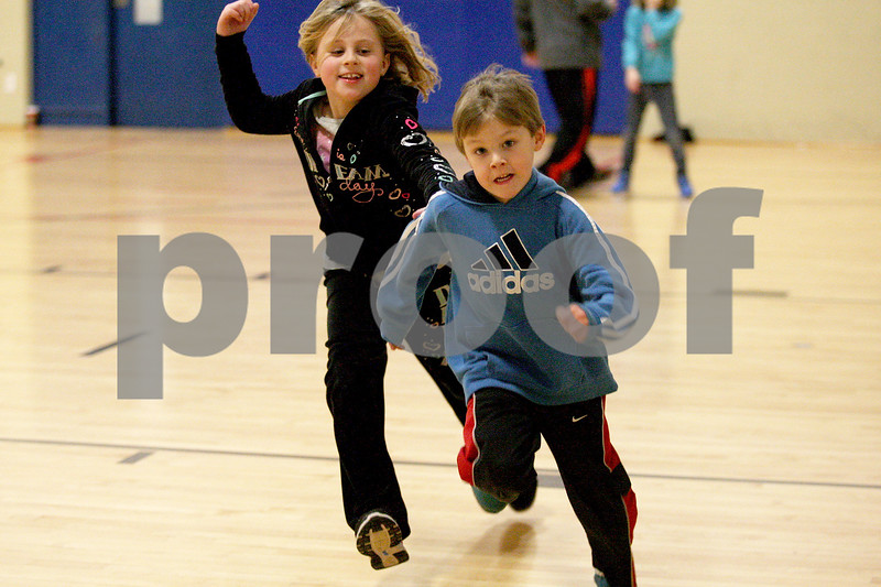 Monica Maschak - mmaschak@shawmedia.com<br /> Molly Livingston, 9, chases Alex Pero, 6, in a game of tag during the No School, No Problem program at Kishwaukee YMCA on Tuesday, January 7, 2014. The program is offered to kids with working parents when schools are closed.