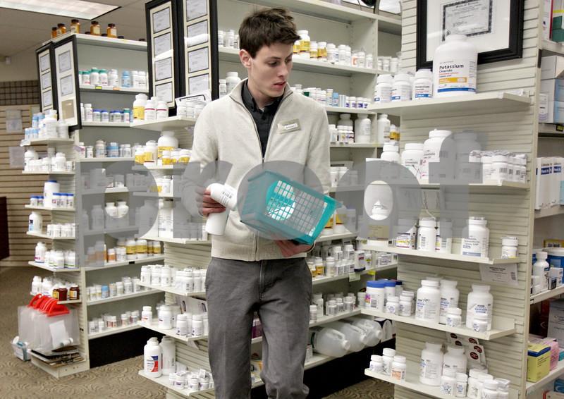 Monica Maschak - mmaschak@shawmedia.com<br /> Pharmacy Technician Marshall Lubbers places drugs back on the shelves at Lehan Drugs on Thursday, January 2, 2014.