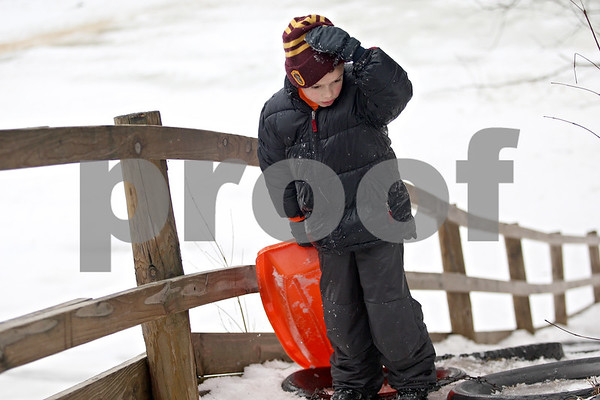 Monica Maschak - mmaschak@shawmedia.com<br /> Cooper Warren, 7, climbs up the icy makeshift steps after sledding down the hill at the Russell Woods Forest Preserve in Genoa on Saturday, January 11, 2014.