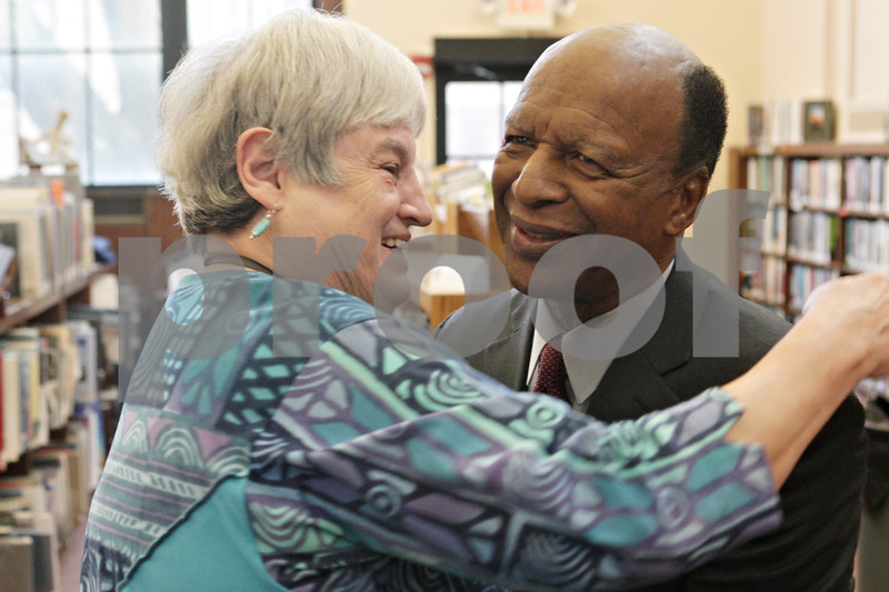 Rob Winner – rwinner@shawmedia.com<br /> <br /> Carolyn Tatman (left) of the DeKalb Public Library hugs Secretary of State Jesse White at the library on Monday, Jan. 13, 2014. White was in DeKalb to present the library with an $11.6 million grant check for expansion.