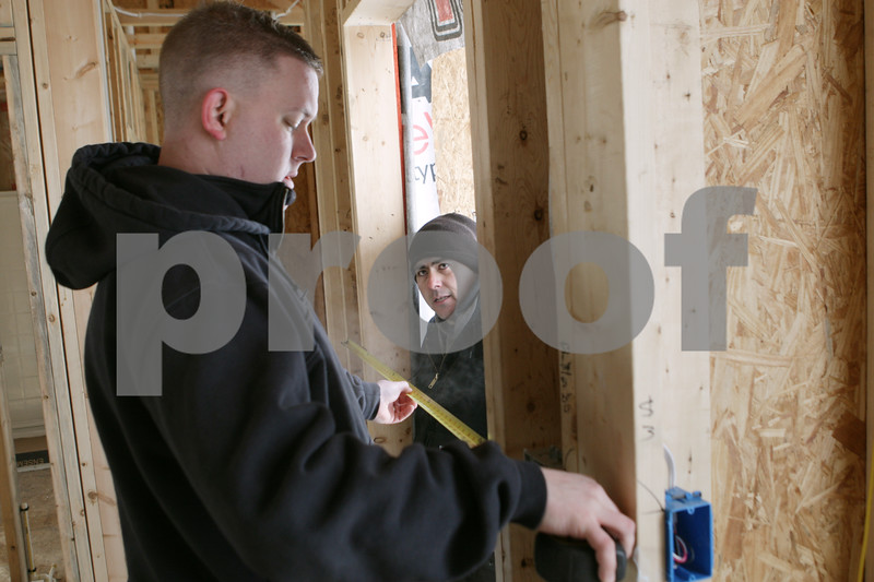 Rob Winner – rwinner@shawmedia.com<br /> <br /> Jim Work (left), owner of Silverthorne Homebuilders, and Jose Garcia, a subcontractor, discuss the measurements of a doorframe during the construction of a new home in the North Grove Crossings subdivision in Sycamore, Ill., Thursday, Jan. 9, 2014.