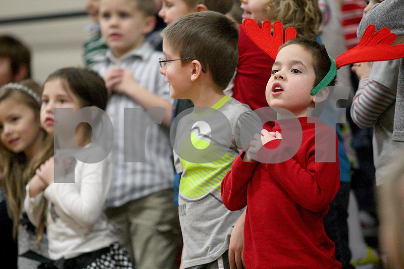 "Monica Maschak - mmaschak@shawmedia.com<br /> Aaron Jindrich sings, ""Melton, the Warm-Hearted Snowman,"" with his classmates during Hiawatha Elementary's kindergarten through second grade Winter Music Program on Wednesday, January 15, 2014."