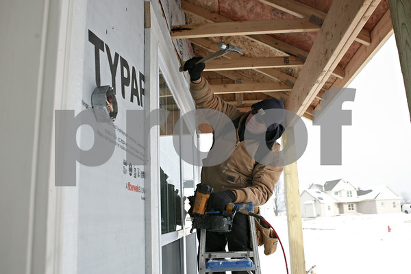 Rob Winner – rwinner@shawmedia.com<br /> <br /> Steve Benson, a subcontractor of Silverthorne Homebuilders, installs exterior trim and siding during the construction of a new home in the North Grove Crossings subdivision in Sycamore, Ill., Thursday, Jan. 9, 2014.