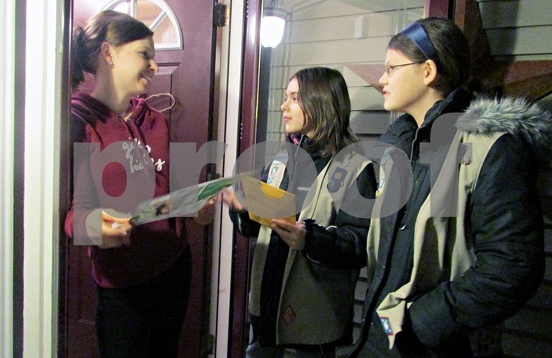 Katie Dahlstrom – kdahlstrom@shawmedia.com<br /> <br /> Genoa Girl Scouts Morgan Siers (center) and Savannah Cravatta sell Girl Scout cookies to their neighbor Brooke Bright on Thursday night outside Bright's home.