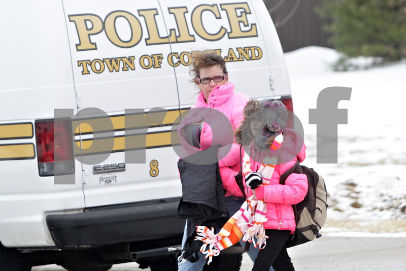 Rob Winner – rwinner@shawmedia.com<br /> <br /> DaNee Walker leaves Cortland Elementary School in Cortland, Ill., with her daughter Paisley, 10, on Tuesday, Jan. 14, 2014. Gas released from the nearby landfill got caught in the school's ventilation system making staff and students nauseous. Emergency personnel from fire departments including Cortland, DeKalb, Sycamore, Maple Park-Countryside, Elburn, Burlington, Hinckley and Genoa-Kingston were seen at the school.