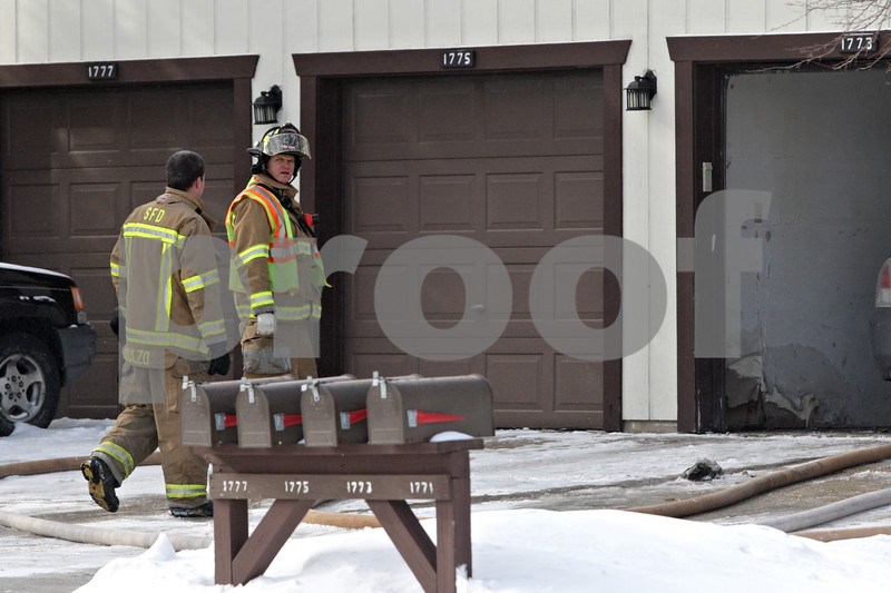 Rob Winner – rwinner@shawmedia.com<br /> <br /> Two Sycamore firefighters are seen outside a town home located on the 1700 block of Longwood Drive in Sycamore, Ill., Friday, Jan. 24, 2014.