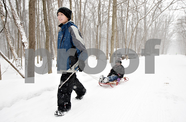 Monica Maschak - mmaschak@shawmedia.com<br /> Robbie Emmens, 10, and pulls his sister, Audrey Emmens, 6, down a snowy-covered road at the annual Winterfest hosted by the University of Illinois Extension at the Natural Resource Education Center in Russell Woods Forest Preserve in Genoa on Saturday, January 18, 2014.