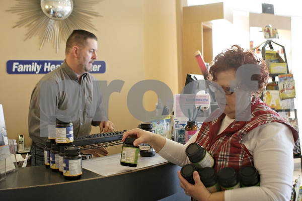 Rob Winner – rwinner@shawmedia.com<br /> <br /> Linda DeLap (front) stocks bottles of vitamins while working with Family Health Center owner David Butts at the store's location in Sycamore, Ill., Monday, Jan. 20, 2014.