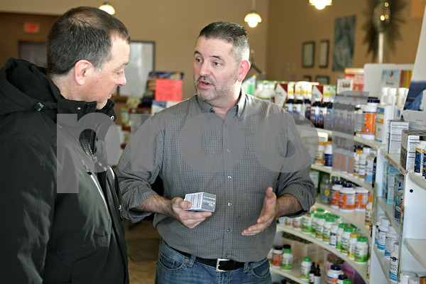 Rob Winner – rwinner@shawmedia.com<br /> <br /> Roger Smith (left) of Sandwich listens to David Butts as he explains the benefits of fish oil at his store, Family Health Center, in Sycamore, Ill., Monday, Jan. 20, 2014.
