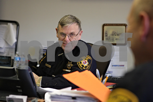 Rob Winner – rwinner@shawmedia.com<br /> <br /> DeKalb County Sheriff Roger Scott is seen in his office in Sycamore, Ill., during a meeting on Tuesday, Jan. 28, 2014. Scott, who began in the communications division and has been elected sheriff seven times, was recognized for 45 years of service at a recent county board meeting.