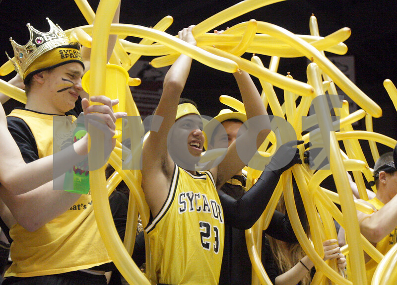 Monica Maschak - mmaschak@shawmedia.com<br /> Kendryck Rand, a Sycamore senior, passes yellow balloons back to his student-section peers during the Sycamore versus DeKalb girls and boys basketball games at the Convocation Center on Friday, January 31, 2014.