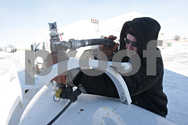 Rob Winner – rwinner@shawmedia.com<br /> <br /> Gary Metcalf of Conserv FS attaches a hose from his truck to a propane tank before filling the tank at a DeKalb business on Monday, Jan. 27, 2014.