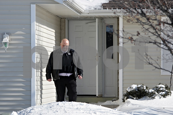 Rob Winner – rwinner@shawmedia.com<br /> <br /> A police officer is seen leaving a home on the 1000 block of Quail Run in DeKalb, Ill., after a report of shots fired on Tuesday, Jan. 28, 2014.