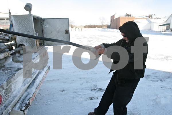 Rob Winner – rwinner@shawmedia.com<br /> <br /> Gary Metcalf of Conserv FS pulls a hose from truck before filling a propane tank at a DeKalb business on Monday, Jan. 27, 2014.