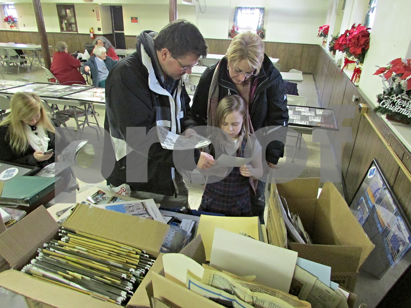 Dave Steimel, Lisa Holiday and her daughter Isabella, 8, look though pictures in the former St. Mary School in DeKalb on Sunday.