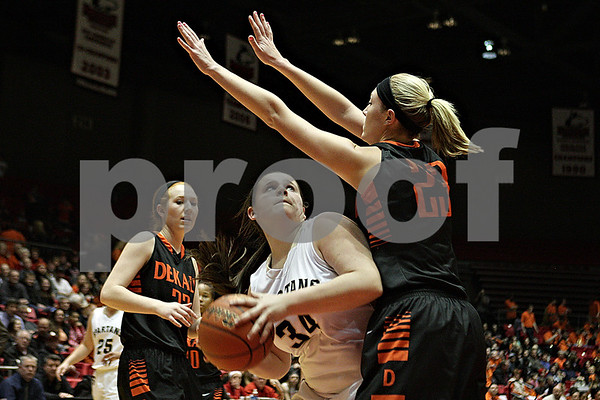Rob Winner – rwinner@shawmedia.com<br /> <br /> Sycamore's Kayley Aase (34) looks to shoot as DeKalb's Madelyne Johnson (23) provides pressure during the third quarter at the Convocation Center in DeKalb, Ill., Friday, Jan. 31, 2014. DeKalb defeated Sycamore, 46-42.