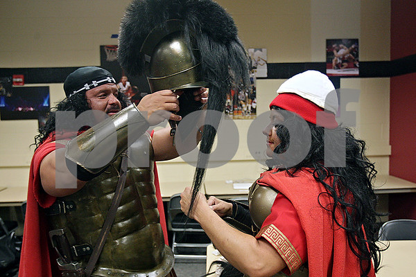 Rob Winner – rwinner@shawmedia.com<br /> <br /> Michael Colweck (left) of Elburn helps put a helmet on his wife, Karen, while dressing up as Spartans before the basketball games between DeKalb and Sycamore at the Convocation Center in DeKalb, lll., Friday, Jan. 31, 2014.