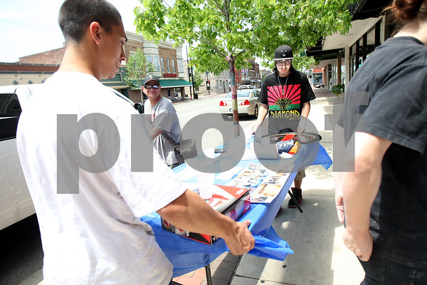 Monica Maschak - mmaschak@shawmedia.com<br /> Jordan Pennington (left) and Alex Valdez carry a table of raffle prizes outside on Saturday, May 31, 2014. Students at Ombudsman DeKalb, an alternative high school in DeKalb, hosted a fundraiser for Skateistan, a non-profit that connects youth and education through skateboarding in Afghanistan and Cambodia.