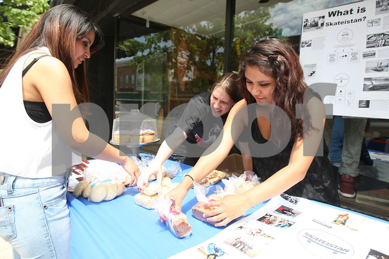 Monica Maschak - mmaschak@shawmedia.com<br /> From left: Yesenia Hernandez, Jennifer Gilley and Silvia Rodriguez set up their freshly-baked treats to sell on Saturday, May 31, 2014. Students at Ombudsman DeKalb, an alternative high school in DeKalb, hosted a fundraiser for Skateistan, a non-profit that connects youth and education through skateboarding in Afghanistan and Cambodia.