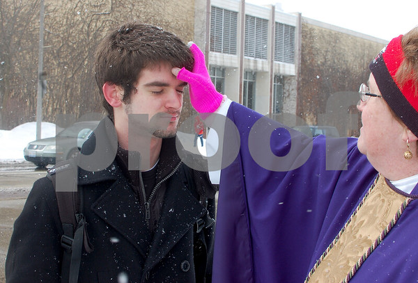 Debbie Behrends - dbehrends@shawmedia.com<br /> Northern Illinois University student Ian Livingston of Aurora, receives Ashes on the Go from the Rev. Amy Fallon at the corner of Normal Road and Lucinda Avenue on Ash Wednesday, March 5, 2014. Dressed in several layers and smiling through the snow, Fallon said she wasn't happy to see her phone weather app showing snow for the day.