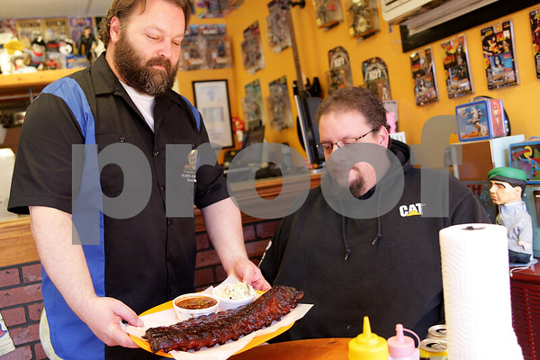 """Monica Maschak - mmaschak@shawmedia.com<br /> Owner Harlan """"Pork Chop"""" Logan serves Chris Woods, of Hinckley, an order of ribs at South Moon Barbeque on Thursday, February 27, 2014. By mid-March, the barbecue shop will move to a bigger location down the road."""