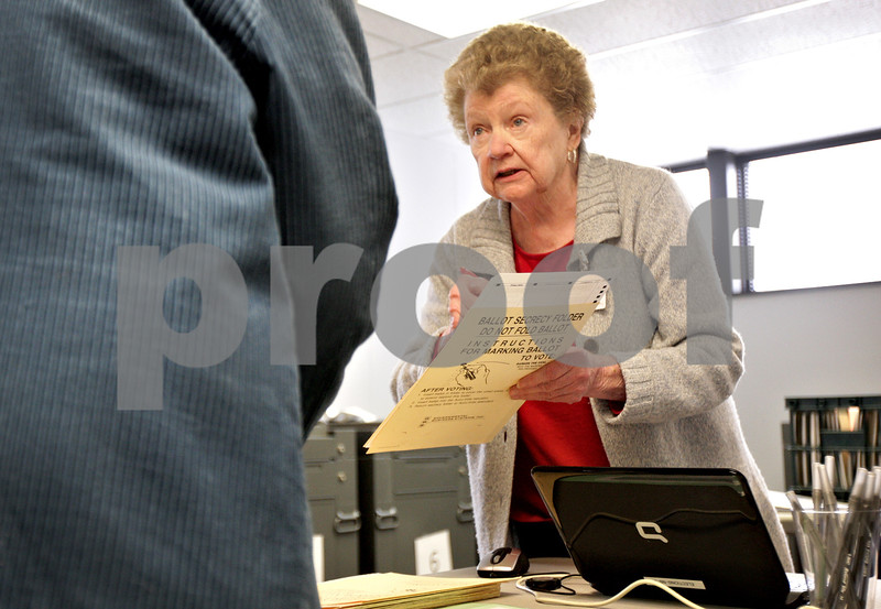Monica Maschak - mmaschak@shawmedia.com<br /> Election Judge Catherine Cwiklinski exlains the ballot to a voter at the DeKalb County Administrative Building on Friday, March 7, 2014.
