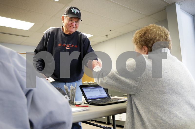 Monica Maschak - mmaschak@shawmedia.com<br /> Sycamore resident Donald Clayberg hands his photo identification card to election judge Catherine Cwiklinski to begin the voting process at the DeKalb County Administrative Building on Friday, March 7, 2014.