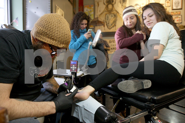 Monica Maschak - mmaschak@shawmedia.com<br /> Co-Owner Chris May tattoos a design on the foot of Elsie Vazquez, 18, as she holds her friend Alejandra Medina's hand at Proton Tattoo Shop on Friday, February 28, 2014. This was Vazquez's first tattoo.