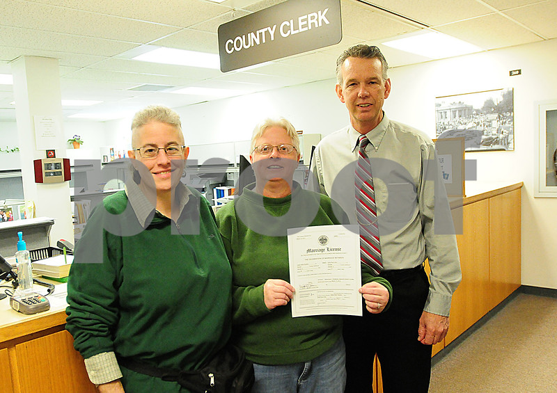 Danielle Guerra - dguerra@shawmedia  Jaelyn Paulsen (left), partner Darla Cook (center), and Dekalb County Clerk and Recorder Doug Johnson pose for a picture after Johnson signed the first same sex marriage license in DeKalb County on Thursday.