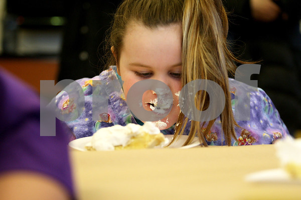 Monica Maschak - mmaschak@shawmedia.com<br /> Tiffany Heath, 7, devours a banana cream pie during a pie-eating contest in honor of Pi Day at Sycamore Library on Friday, March 14, 2014.
