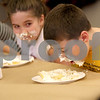 Monica Maschak - mmaschak@shawmedia.com<br /> Kameron Schroeder, 9, attacks a piece of banana cream pie to win third place during a pie-eating contest in honor of Pi Day at Sycamore Library on Friday, March 14, 2014.