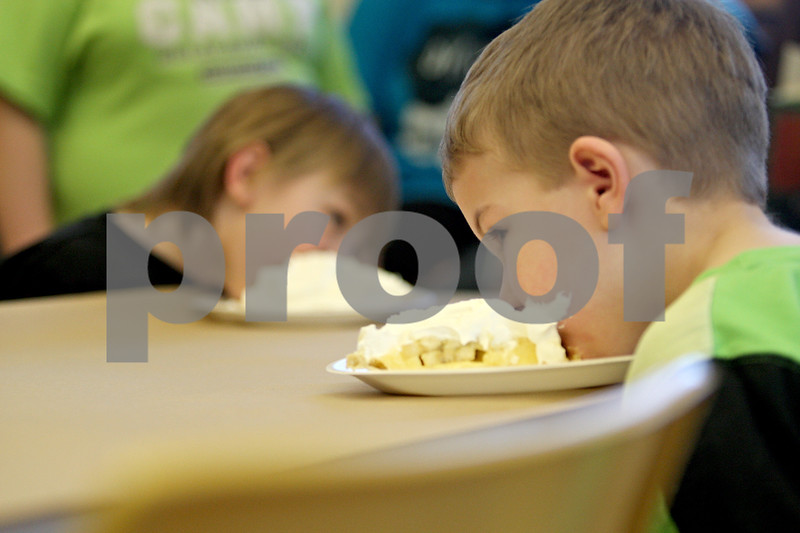 Monica Maschak - mmaschak@shawmedia.com<br /> Peyton Heffley, 7, dives in to his piece of banana cream pie during a pie-eating contest in honor of Pi Day at Sycamore Library on Friday, March 14, 2014.