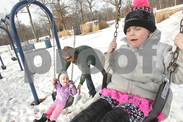 Danielle Guerra - dguerra@shawmedia.com\<br /> Cammie Laws (left), 22 months, swings with the help of her mother Sommer Laws, next to her sister Gabbie Laws, 5, in Hopkins Park in DeKalb Monday afternoon.  Laws said the weather warm up was much needed after the winter gave her family cabin fever.