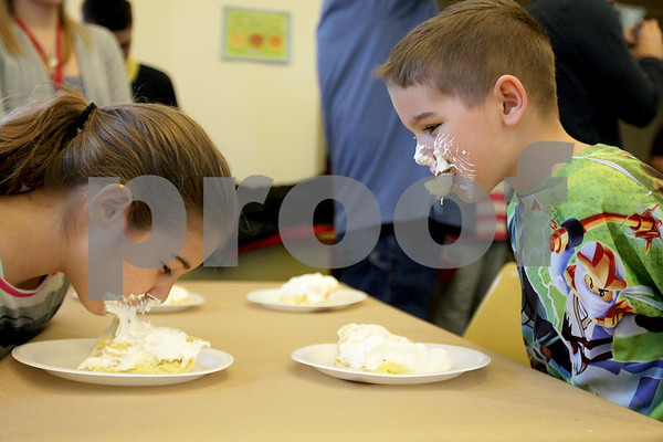 Monica Maschak - mmaschak@shawmedia.com<br /> Ayden Latsis, 6, watches sister Ava Latsis, 8, as they both chow down on banana cream pie during a pie-eating contest in honor of Pi Day at Sycamore Library on Friday, March 14, 2014.