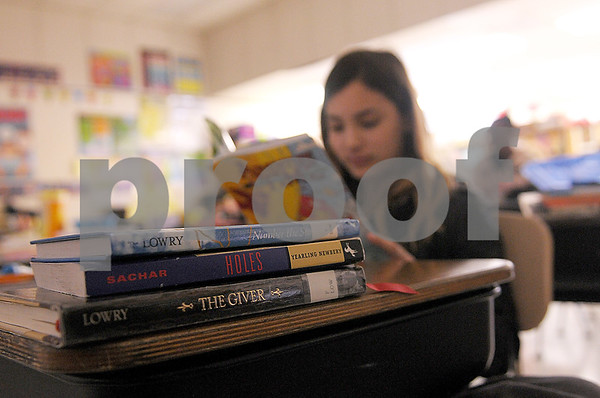 "Danielle Guerra - dguerra@shawmedia<br /> A stack of books sits on Riley Saghu's desk while she reads ""Adventure Time"" during an activity time in Dianne Carlson's fifth-grade class at Tyler Elementary in DeKalb on Thursday.  Reading specialist Stacie Keegan won a $500 grant from Target to build the libraries in individual classrooms."