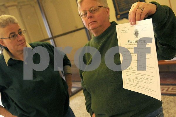 Danielle Guerra - dguerra@shawmedia.com  Darla Cook (right) holds up her and partner Jaelyn Paulsen's freshley signed marriage license while inside the DeKalb County Courthouse Thursday morning.