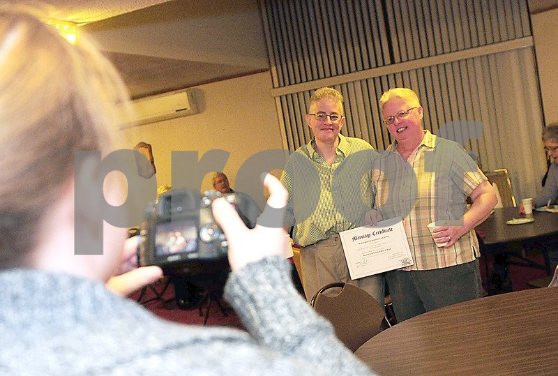 Danielle Guerra - dguerra@shawmedia   Photographer Jennifer Morrow takes a picture of Jaelyn Paulsen (right) and Darla Cook (left) with their marriage license after they were married at the Mayfield Congregational Church UCC in Sycamore Monday night.
