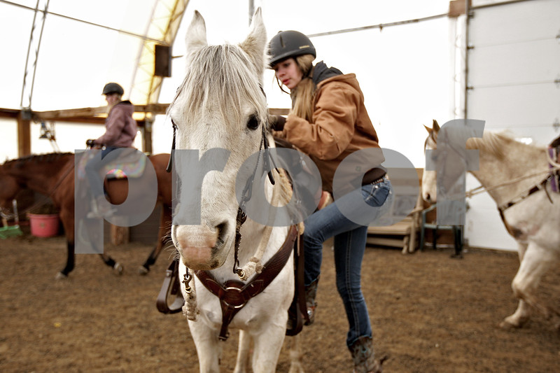 Monica Maschak - mmaschak@shawmedia.com<br /> Olivia Willrett, 15, mounts her horse, Windsor, during an Advanced Spring Break Horse Camp at Runaway Ranch in Sycamore on Tuesday, March 25, 2014.