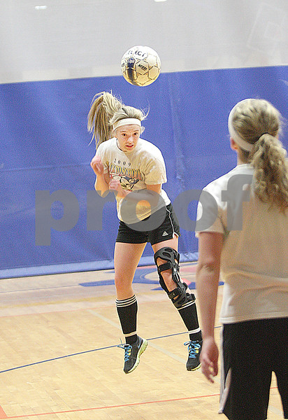 Danielle Guerra - dguerra@shawmedia.com  Genoa-Kingston junior midfielder Ashley Grimm heads a ball during a drill Tuesday morning in the gym.  Grimm did not play all of last season because of a torn ACL but went to every game and was around the team at practices for support.